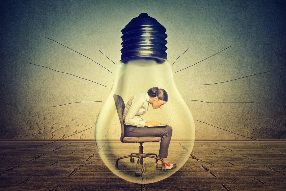 Woman working on laptop computer sitting inside electric light bulb isolated on gray office wall background