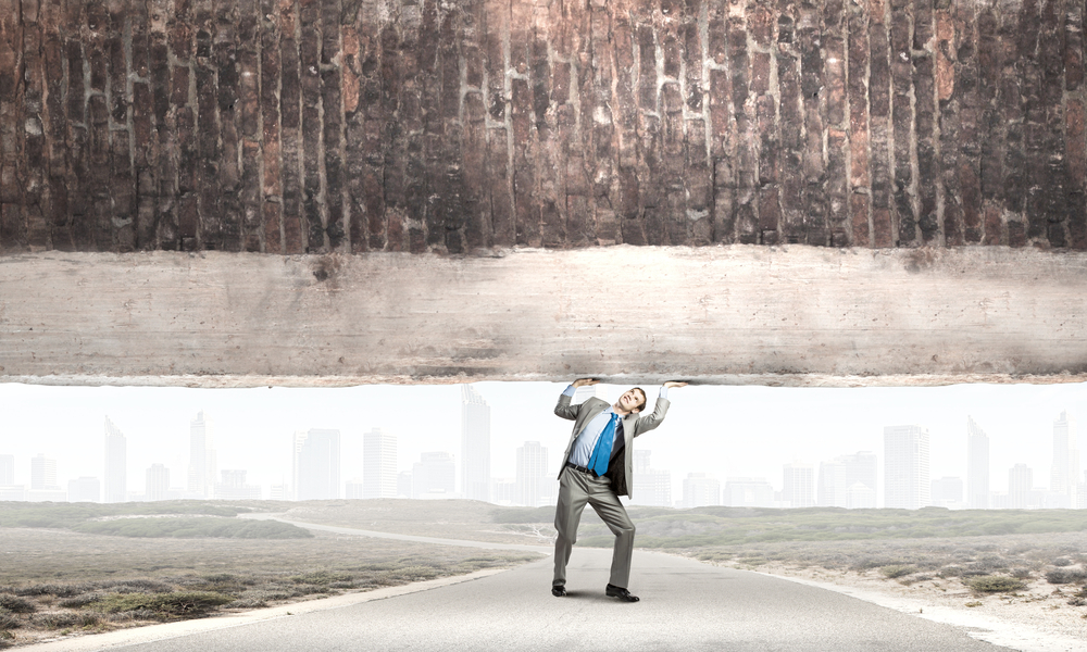 Young powerful businessman lifting brick wall above head