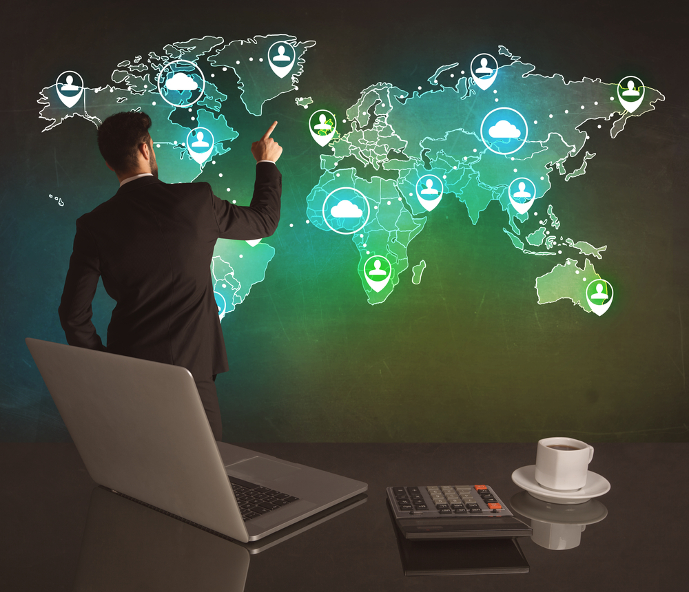 A young business manager working on a global sales strategy and drawing on illustrated map of the world concept