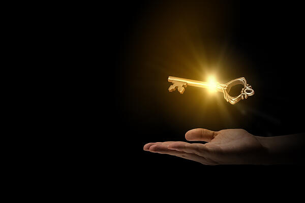 Close up of human hand holding golden key-1