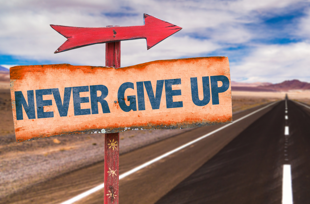 Never Give Up sign with road background