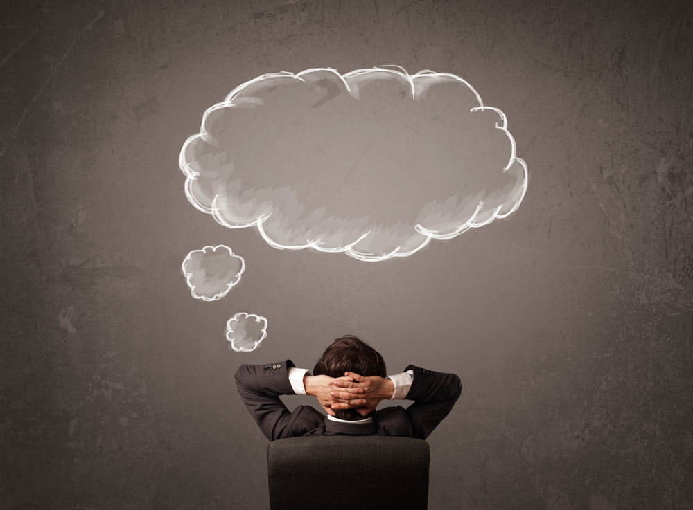 Young businessman sitting in office chair in front of a wall with cloud thought sketched on a chalkboard above his head-1
