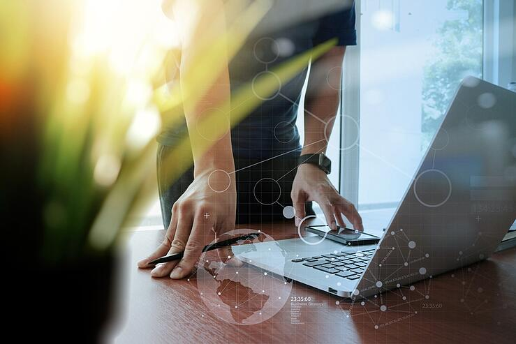 designer hand working laptop with green plant foreground and digital social diagram layers on wooden desk in office